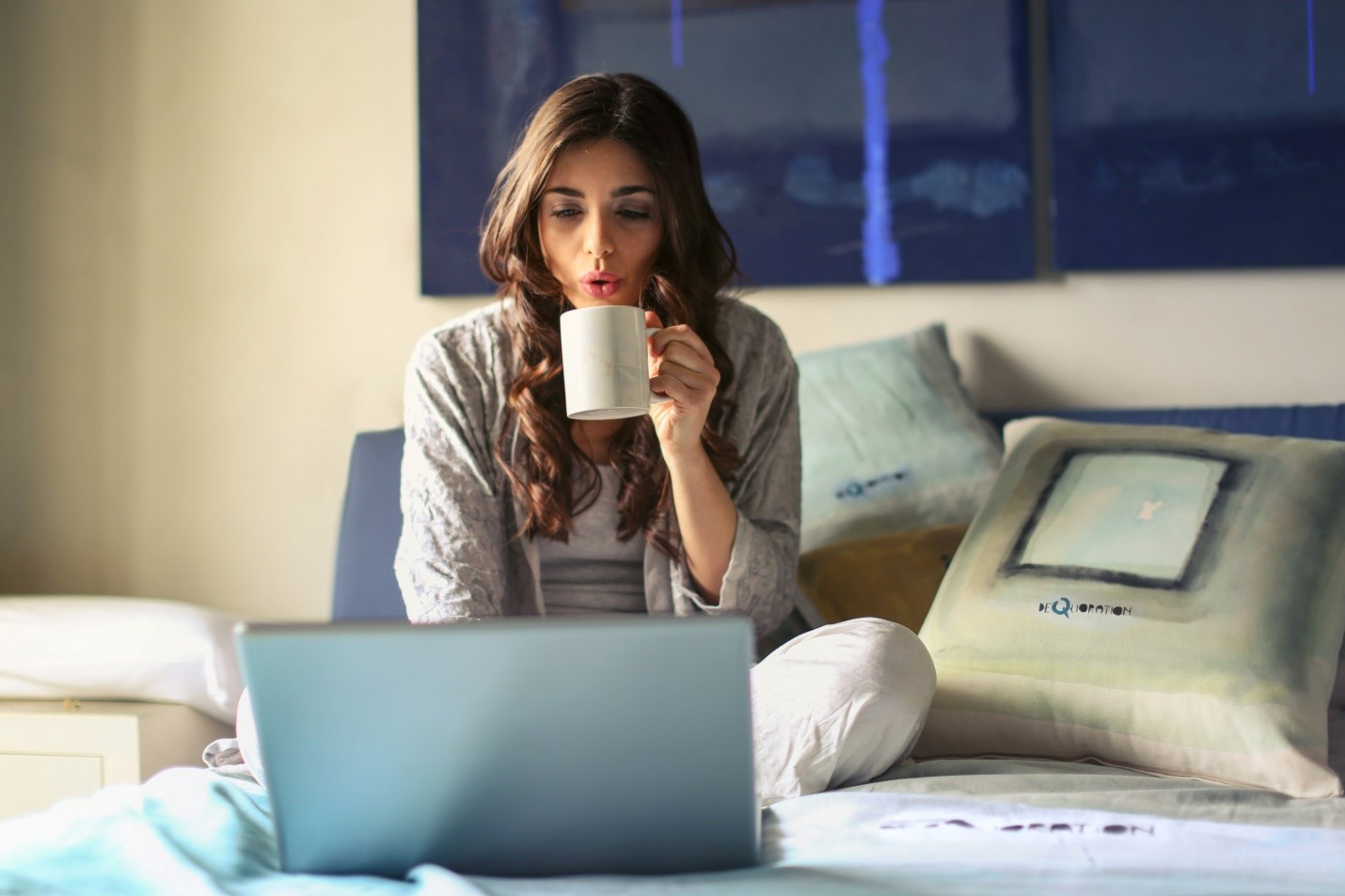 Career Break - image of a woman sipping coffee and working on her laptop