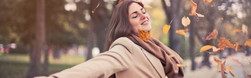 Image of a happy woman with arms stretched out enjoying the fall weather - Decoding stress