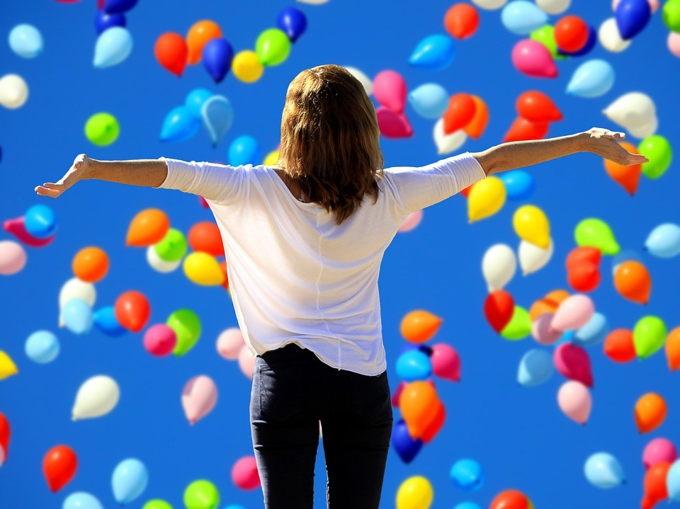 Self-confidence - woman looking at the sky filled with colored balloons