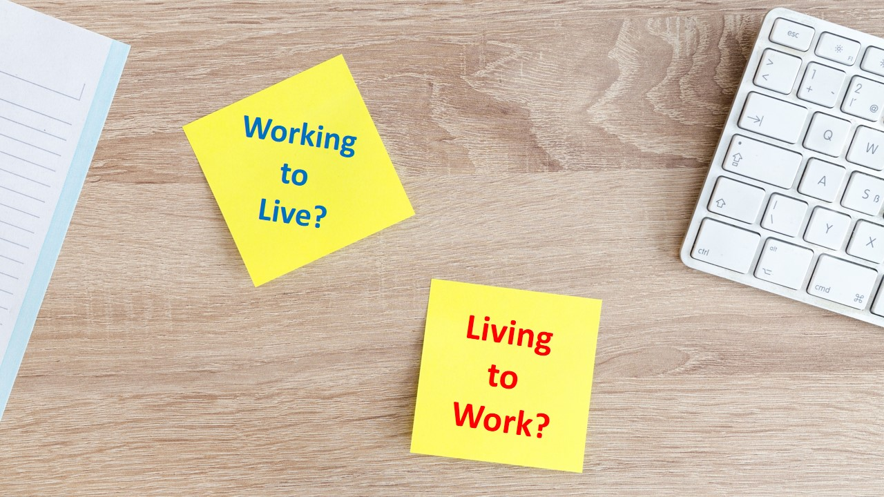 image of a laptop key board and post note on a table reading - Working to Live, Living to Work